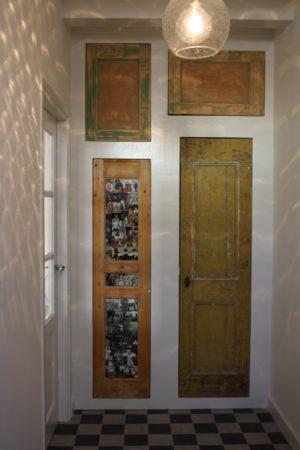 Hergebruikte deuren in hal visserswoning op Vlieland. Een deur zijn paneeltjes vervangen door glas met foto's er achter.
